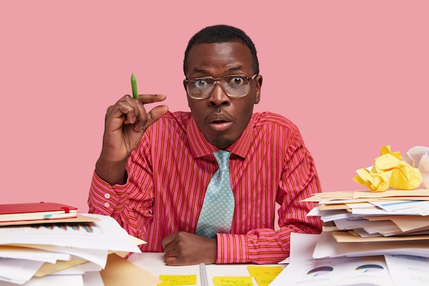 La photo d'un homme mécontent étourdi fait un geste de taille, montre à quel point il a besoin d'attention et d'aide, termine la tâche, modélise au bureau