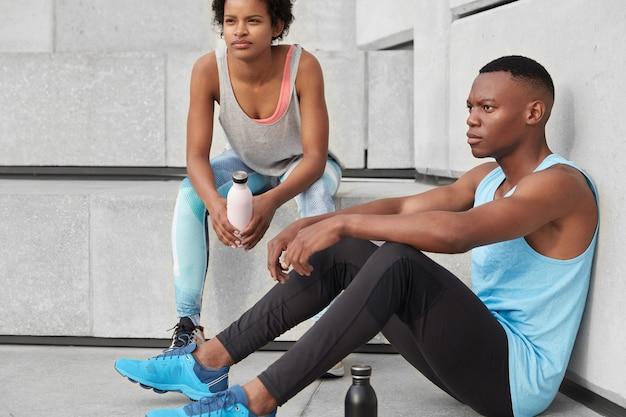 Photo d'un homme motivé à la peau sombre et de sa compagne, posent ensemble dans les escaliers, font une pause après un entraînement cardio en plein air, boivent de l'eau, ont une silhouette athlétique, courent. concept de mode de vie