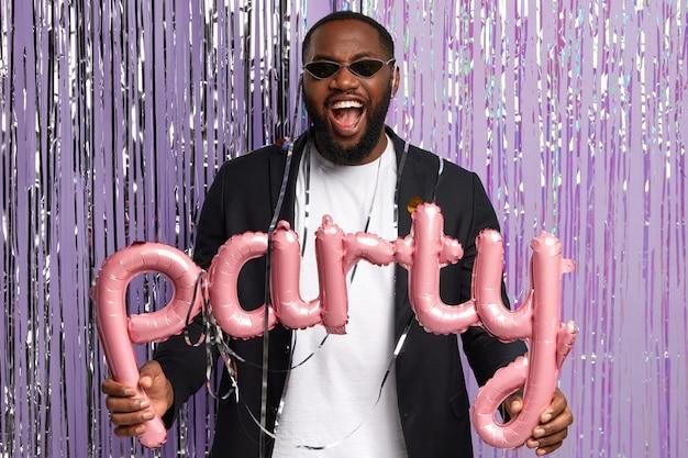 Photo d'un homme noir ravi porte des nuances à la mode et un costume élégant, célèbre la fête d'adieu, tient des décorations, se tient contre un mur violet avec des guirlandes, rencontre des invités de bonne humeur.
