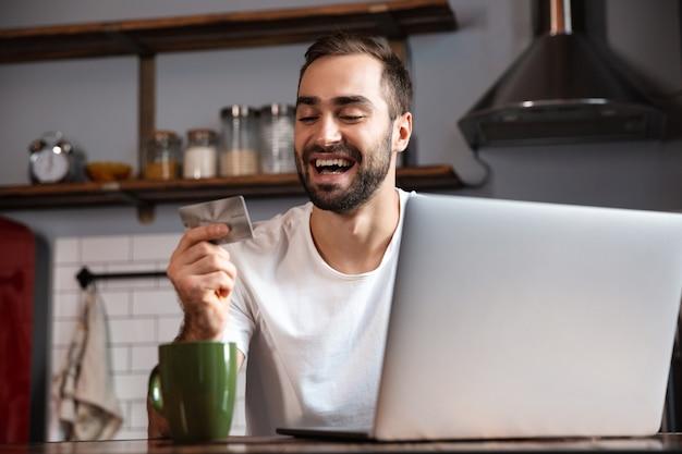 Photo d'un homme optimiste de 30 ans portant un t-shirt décontracté à l'aide d'un ordinateur portable argenté alors qu'il était assis à table dans un appartement moderne