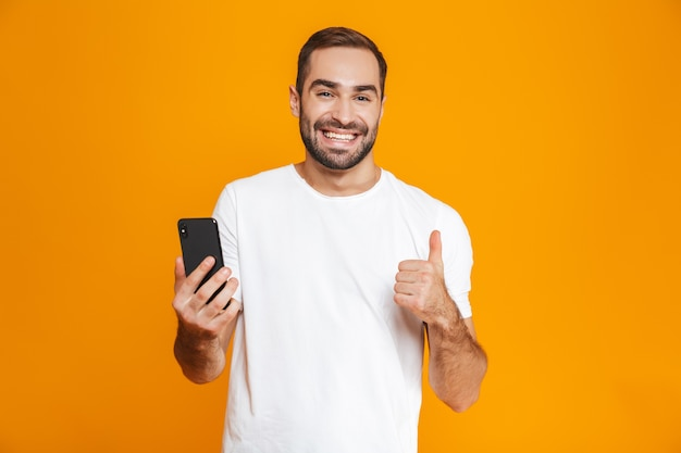 Photo d'un homme positif de 30 ans en tenue décontractée souriant et tenant un smartphone, isolé