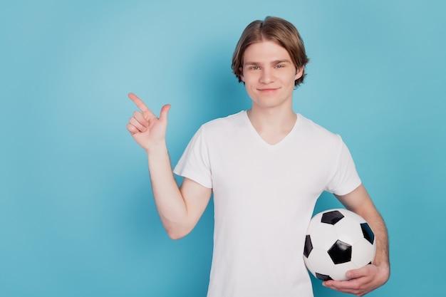 Photo de l'homme positif pointer l'espace vide tenant un ballon de football fond bleu isolé