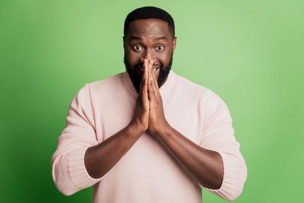 Photo d'un homme positif reconnaissant un geste implorant demander de l'aide porter une chemise blanche sur fond vert