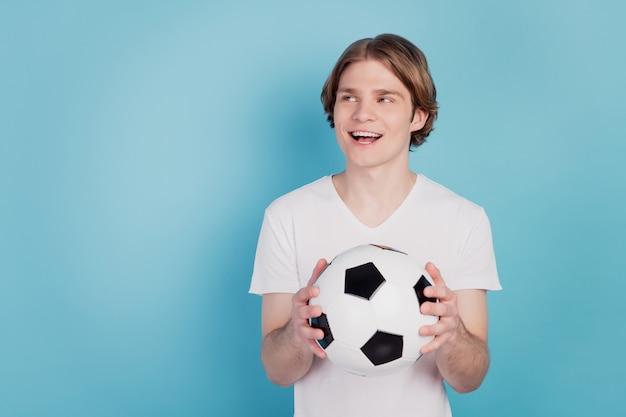 Photo d'un homme positif regarde un espace vide tenant un ballon de football sur fond bleu isolé