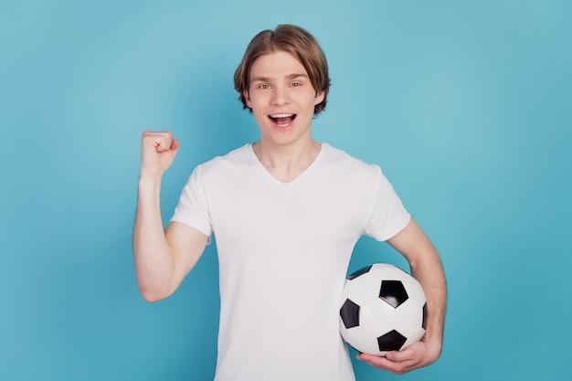 Photo d'un homme positif tenant un ballon de football lever les poings sur fond bleu isolé