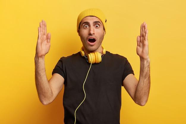 Photo d'un homme de race blanche impressionné fait un grand signe avec les deux mains, forme un objet assez énorme, impressionné par la taille