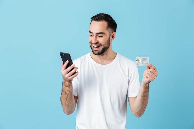 Photo d'un homme de race blanche portant un t-shirt basique souriant tout en tenant un smartphone et une carte de crédit isolés sur bleu