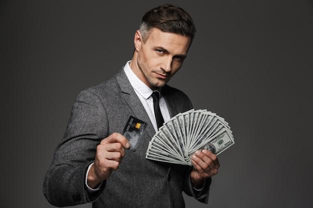 Photo d'un homme riche de 30 ans en costume d'affaires tenant un fan d'argent en dollars et d'argent numérique sur carte de crédit, isolé sur mur gris