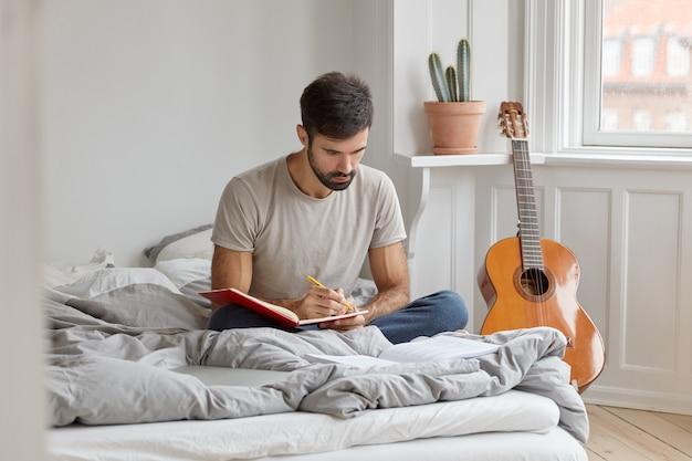 Photo d'un homme sérieux avec des poils noirs, écrit une histoire dans son journal sur ce qui s'est passé pendant la journée, s'assoit les jambes croisées au lit, porte des vêtements décontractés, a un jour de congé ou un week-end. informations sur les enregistrements masculins