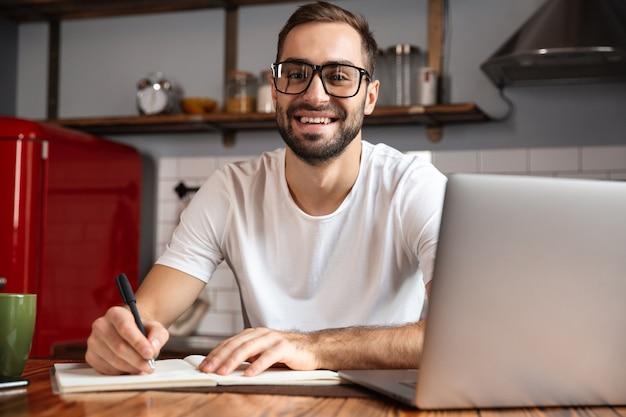 Photo d'un homme souriant de 30 ans portant des lunettes d'écrire des notes tout en utilisant un ordinateur portable argenté sur la table de cuisine
