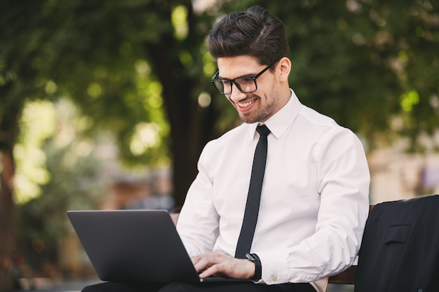 Photo d'un homme souriant en costume professionnel assis sur un banc dans un parc verdoyant et travaillant sur un ordinateur portable pendant la journée ensoleillée