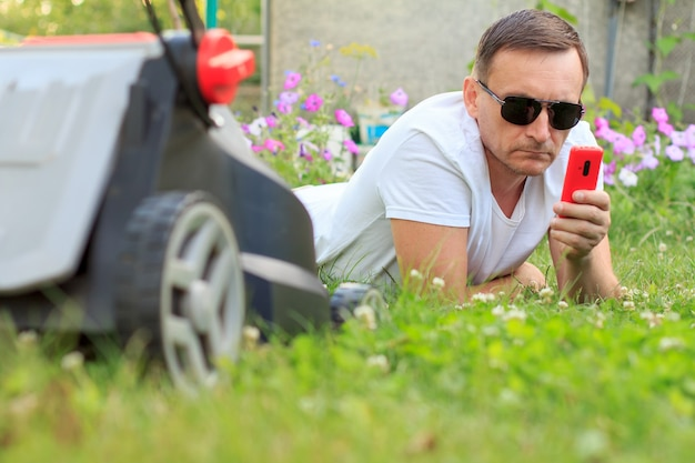Photo d'homme en t-shirt blanc et lunettes de soleil avec téléphone portable allongé sur l'herbe avec tondeuse à gazon