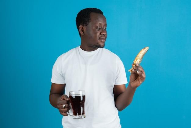 Photo d'un homme en t-shirt blanc tenant du poisson séché avec une tasse de vin en verre contre le mur bleu