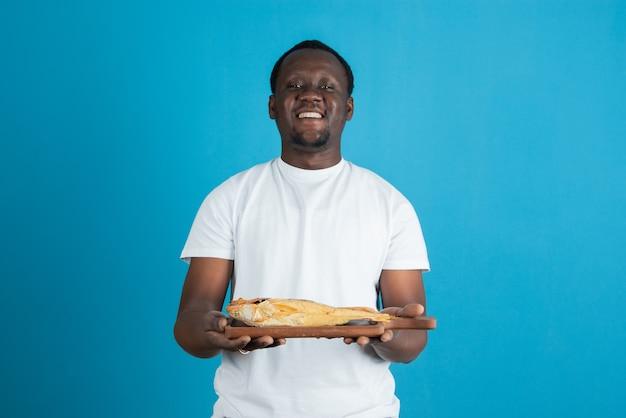 Photo d'un homme en t-shirt blanc tenant une planche à découper en bois avec du poisson séché contre un mur bleu