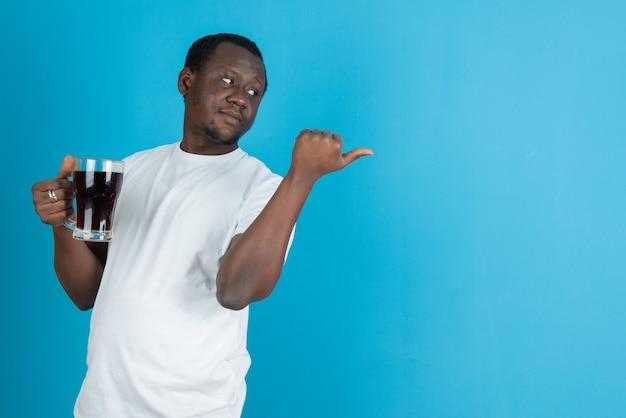 Photo d'un homme en t-shirt blanc tenant une tasse de vin en verre contre un mur bleu