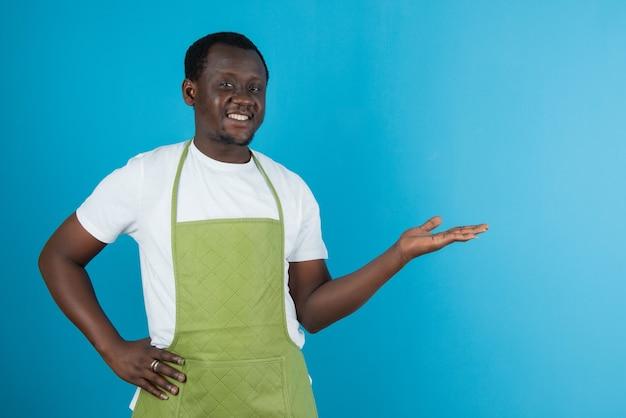 Photo d'un homme en tablier vert montrant une paume ouverte contre un mur bleu
