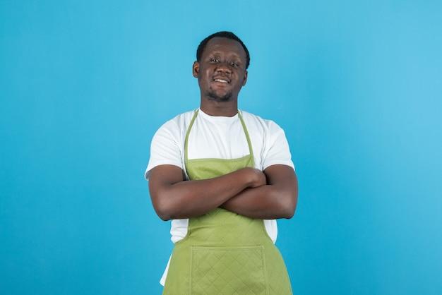 Photo d'un homme en tablier vert posant les bras croisés contre le mur bleu