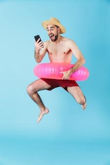 Photo d'un homme touristique torse nu drôle portant un anneau en caoutchouc souriant et tenant un téléphone portable isolé sur bleu