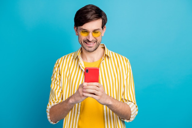 Photo d'un homme de type positif blogueur touristique utilise un type de smartphone le week-end d'été sur les médias sociaux commenter le style d'usure tenue blanche jaune isolée sur fond de couleur bleu