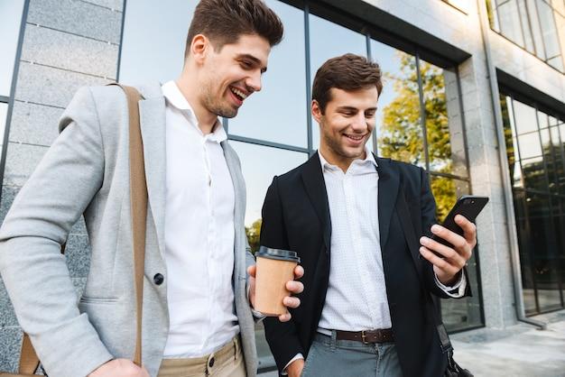 Photo d'hommes d'affaires européens en costumes à l'aide de smartphones, tout en se tenant à l'extérieur près du bâtiment avec du café à emporter