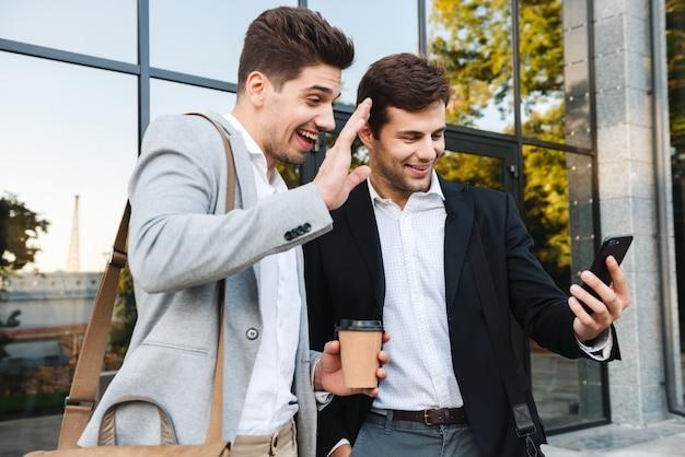 Photo d'hommes d'affaires heureux en costumes à l'aide de smartphones, tout en se tenant à l'extérieur près du bâtiment avec du café à emporter