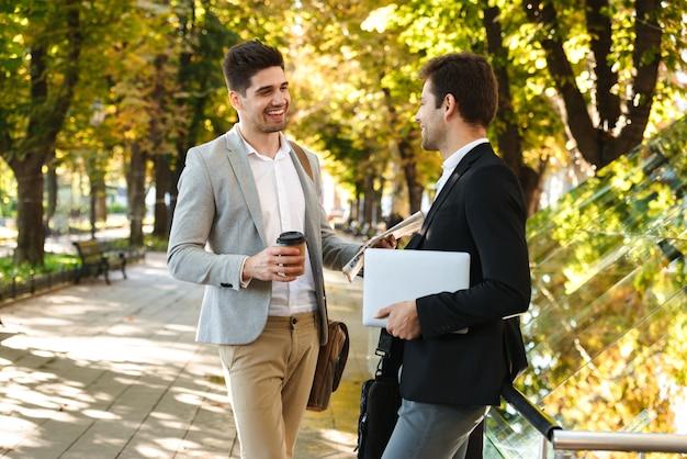 Photo d'hommes d'affaires souriants en costumes marchant en plein air à travers le parc verdoyant avec café à emporter et ordinateur portable, pendant la journée ensoleillée