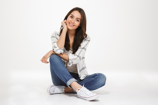 Photo horizontale de femme brune aux cheveux bruns assis avec les jambes croisées sur le sol et regardant la caméra avec le sourire, isolé sur mur blanc