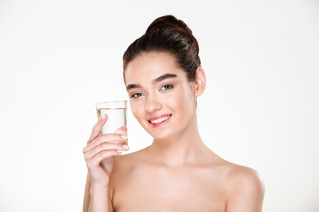 Photo horizontale d'une femme heureuse et en bonne santé étant à moitié nue en buvant de l'eau minarale à partir de verre transparent avec sourire