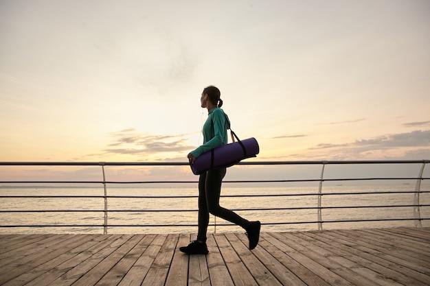 Photo horizontale d'une femme qui marche au bord de la mer le matin, va pratiquer le yoga et fait des étirements matinaux, tenant un tapis de yoga violet et détourne le regard.