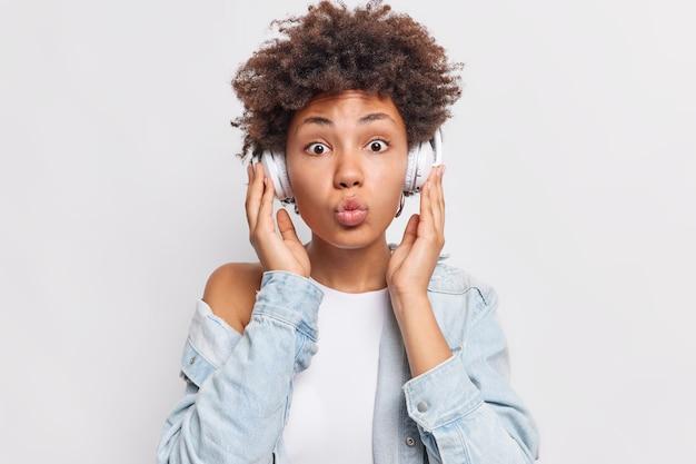 Une photo horizontale d'une jolie femme aux cheveux bouclés garde les lèvres arrondies et écoute la piste audio préférée via un casque sans fil porte une chemise en jean élégante isolée sur un mur blanc