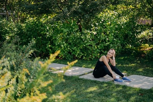 Une photo horizontale pleine longueur d'une femme sportive brune heureuse écoute une liste de lecture de motivation avant de commencer à courir vêtue de poses de vêtements actifs sur le chemin utilise l'application en ligne concept sport et bien-être