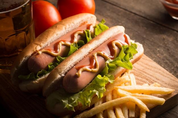 Photo de hot-dog grillé au barbecue avec de la moutarde jaune et du ketchup sur fond de bois. sandwich au hot dog avec frites de pommes de terre et sauces.