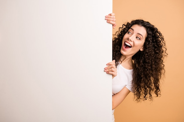 Photo d'une incroyable dame tenant une grande pancarte blanche présentant des informations de nouveauté ne pas croire les prix de vente porter des vêtements décontractés blancs fond de couleur pastel beige