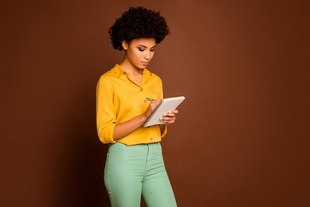 Photo de l'incroyable peau foncée curly lady auteur regarder attentivement le journal en notant les pensées créatives écrivant des commentaires porter chemise jaune pantalon vert isolé couleur marron