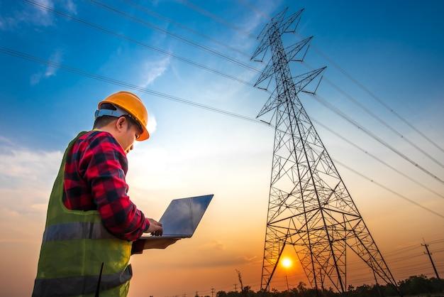 Photo d'un ingénieur électricien à l'aide d'un ordinateur portable debout dans une centrale électrique pour voir le travail de planification en produisant de l'énergie électrique à des électrodes haute tension