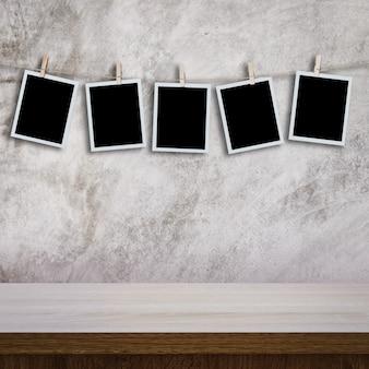 Photo instantanée accroché sur la table en bois et le mur de ciment texture fond avec espace