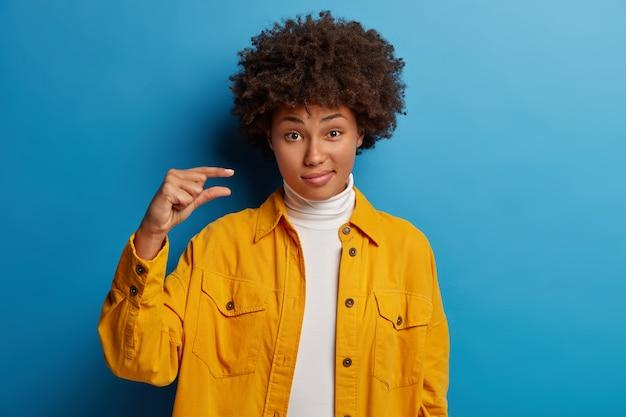Une photo en intérieur d'une belle femme aux cheveux bouclés montre une petite taille peu impressionnante, façonne très peu d'objet, dit qu'il est trop petit, manque un petit pourcentage lors du test de réussite