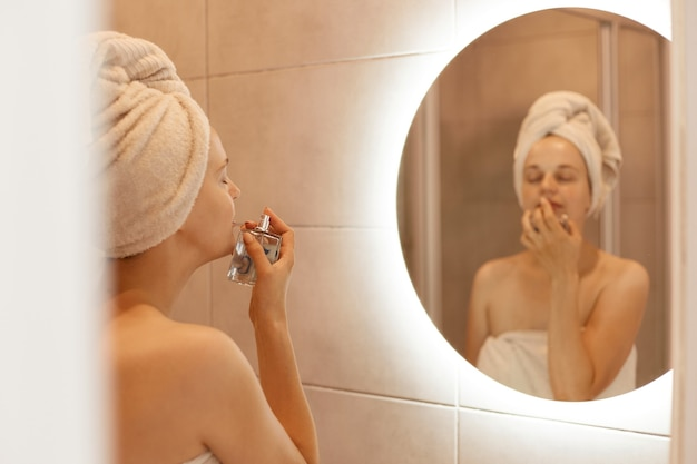 Photo d'intérieur d'une belle femme enveloppée dans une serviette blanche sur la tête, sentant le parfum tout en posant dans la salle de bain, profitant d'une odeur agréable, garde les yeux fermés.