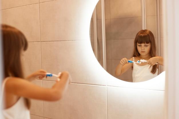 Photo d'intérieur d'une charmante petite fille se brossant les dents dans la salle de bain, pressant le dentifrice hors d'un tube, debout devant le miroir, ayant une expression faciale concentrée.