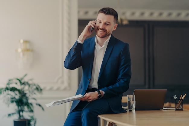 Photo d'intérieur d'un entrepreneur positif vêtu d'un costume formel a une conversation téléphonique pour discuter des problèmes de travail avec le partenaire se penche sur le bureau tient des documents papier se prépare pour la présentation