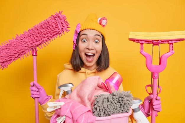 Une photo d'intérieur d'une femme asiatique a un visage très surpris qui garde la bouche grande ouverte et remarque que la pièce sale va tout nettoyer contient des produits de nettoyage se tient près du panier à linge contre le mur jaune
