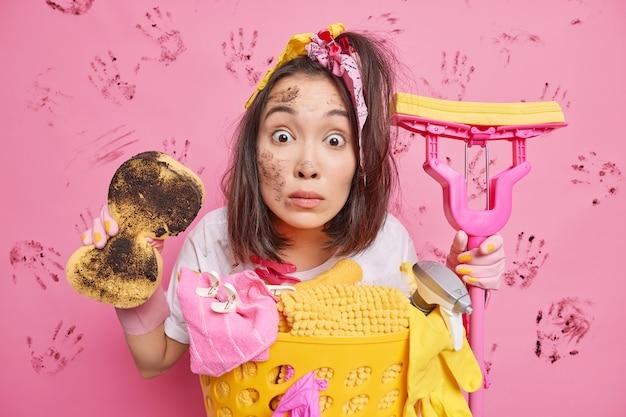 Photo d'intérieur d'une femme au foyer ethnique surprise tenant une éponge sale et une vadrouille occupée à faire le ménage se tient près du panier de linge pose contre le mur rose