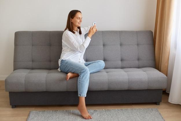 Photo d'intérieur d'une femme aux cheveux noirs portant une chemise blanche et un jean, assise avec un smartphone dans les mains, regardant l'écran de l'appareil, naviguant sur internet ou écrivant un message pour les réseaux sociaux.