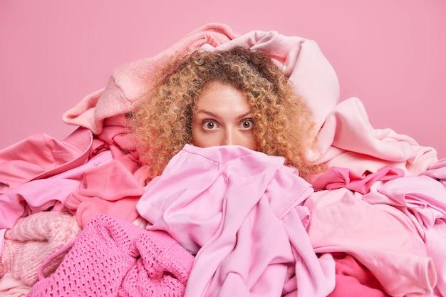 Une photo d'intérieur d'une femme choquée entourée de vêtements roses aide les gens à faire des dons de vêtements à un travail caritatif qui choisit une tenue pour une utilisation ou un recyclage secondaire.