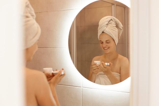 Photo d'intérieur d'une femme souriante hydratant la peau après la douche, tenant de la crème dans les mains, exprimant des émotions heureuses, étant enveloppée dans une serviette, faisant des procédures de spa à la maison.