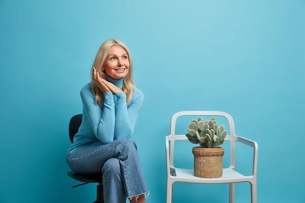 Photo d'intérieur d'une grand-mère rêveuse et ridée qui pose sur une chaise confortable se déplace dans un nouvel appartement près d'un cactus en pot