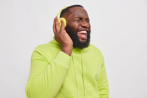 Photo d'intérieur d'un homme barbu noir crie en écoutant de la musique avec un son très fort vêtu d'un sweat à capuche pose contre le mur gris du studio