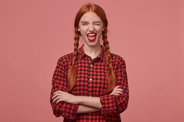 Photo d'intérieur d'une jeune adolescente rousse, garde les mains croisées, sourit largement et fait un clin d'œil avec une expression faciale positive