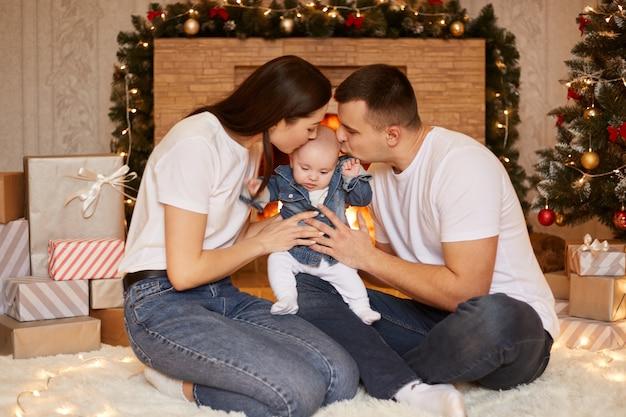 Photo d'intérieur d'une jeune famille heureuse posant dans une salle de fête de noël tout en étant assis sur le sol et embrassant ensemble leur petite fille mignonne, joyeux noël et bonne année.