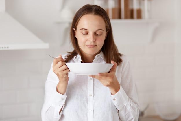 Photo d'intérieur d'une jeune femme adulte affamée et heureuse aux cheveux noirs mangeant dans une assiette le matin, sentant une soupe ou d'autres aliments, posant avec un ensemble de cuisine en arrière-plan.